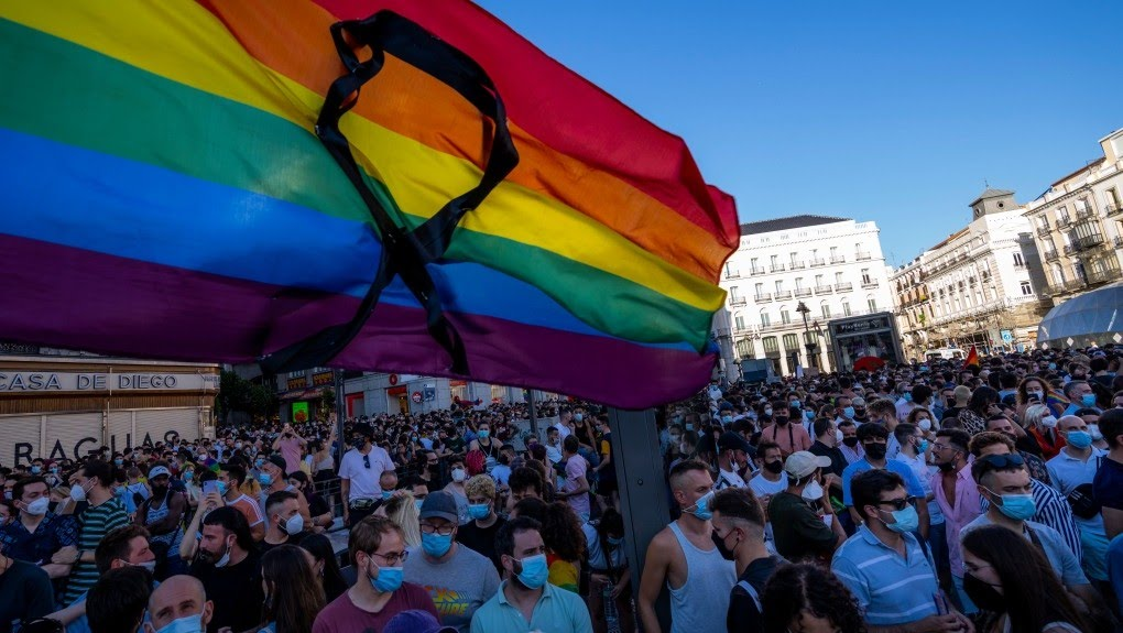 The rainbow flag with a black ribbon flutters during a protest against the killing of Samuel Luiz in the Puerta del Sol in central Madrid, Spain, Monday, July 5, 2021. Authorities in northwestern Spain are asking for time to fully investigate why a 24-year-old man was beaten to death, a crime that has triggered widespread condemnation because friends of the victim claim he was targeted for being gay. LGBTQ activists have called for protests in dozens of cities across Spain later on Monday and members of Spain's left-wing Cabinet have condemned the death of Samuel Luiz in the early hours of Saturday as a hate crime. Police are reviewing surveillance cameras and questioning over a dozen suspects and witnesses who saw how Luiz was beaten to death outside a nightclub in the city of A Coruña. The death comes amid a spike in attacks on LGBTQ people. (AP Photo/Bernat Armangue)